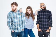 Confident woman standing between two bearded pensive men Stock Photo