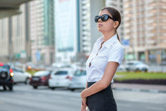 Confident woman. Successful arabic businesswoman standing. In the street in formal attire. Businessman standing near skyscrapers in Dubai downtown in sunglasses Stock Image