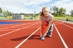 Confident Woman Tying Shoe Lace On Running Tracks Royalty Free Stock Photo