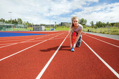 Confident Woman Tying Shoelace On Running Tracks stock images