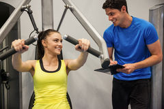 Confident woman using weights machine with trainer Stock Photography