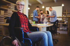 Confident woman on wheelchair while colleagues in background. Portrait of confident women on wheelchair while colleagues in background at creative office Royalty Free Stock Photography