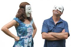 Confident woman wearing a happy face mask looks at at unconfident man who wearing a sad face mask stock photography