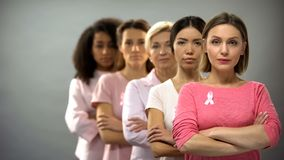 Confident women wearing pink breast cancer awareness ribbons standing in row. Stock photo stock photos