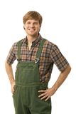 Confident worker. Confident young worker wearing green workwear, standing with arms on hips, smiling. Cutout Stock Image
