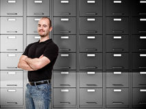 Confident worker. Portrait of caucasian worker and file cabinet background Stock Images