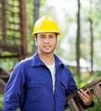Confident Worker Carrying Ladder At Construction Royalty Free Stock Photos
