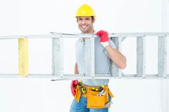 Confident worker carrying step ladder Stock Photography