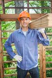 Confident Worker Carrying Tied Wooden Planks Stock Image