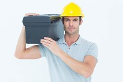 Confident worker carrying tool box on shoulder. Portrait of confident worker carrying tool box on shoulder over white background Royalty Free Stock Photos