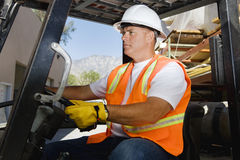 Confident Worker Driving Forklift At Workplace. Confident male industrial worker driving forklift at workplace Royalty Free Stock Photos