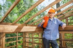 Confident Worker Holding Pipe In Wooden Cabin Stock Images