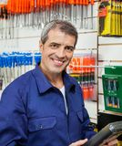 Confident Worker Holding Product In Hardware Store Royalty Free Stock Photo