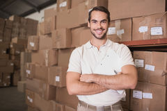 Confident worker smiling in warehouse. Portrait of a confident worker smiling in the warehouse Royalty Free Stock Images