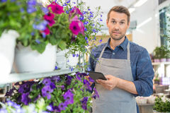 Confident Worker Using Digital Tablet In Flower. Portrait of confident male worker using digital tablet while standing by trolley in flower shop Stock Images