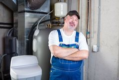 Confident workman or home installer. Standing smiling at the camera with folded arms in a basement utility room Stock Photo