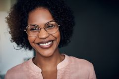 African businesswoman standing in a modern office smiling confidently stock photos