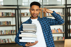 Confident young african male student holding stack of books Stock Images