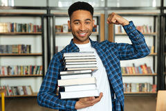 Confident young african male student holding stack of books Royalty Free Stock Image