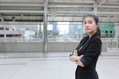 Confident young Asian business woman crossing one`s arms at outside office. Stock Photo