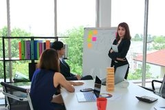Confident young Asian business woman explaining strategies on flip chart to executive in boardroom stock photography