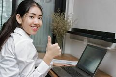 Confident young Asian business woman showing thump up hand sign on office. Stock Photos