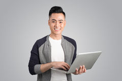 Confident young asian businessman holding laptop Stock Photos