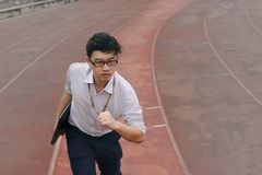Confident young Asian businessman with laptop ready run to forward on race track. Business vision concept. stock photos