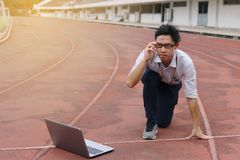 Confident young Asian businessman with laptop ready start position to forward on race track with sunshine effect. Competition and. Vision business concept royalty free stock photography