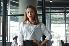 Confident young Asian businesswoman standing in office. Thinking and thoughtful business concept royalty free stock image
