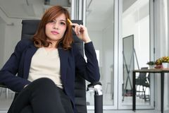 Confident young Asian executive woman sitting and having idea in workplace of office stock photos