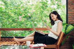 Confident young asian woman in smart casual wear using smartphon Royalty Free Stock Image