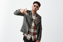 Confident young attractive black-skinned african male with curly hair in trendy leather jacket and sunglasses making gun Royalty Free Stock Photography