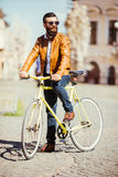 Confident young bearded man in sunglasses riding on his bicycle along the sunny street Royalty Free Stock Photos