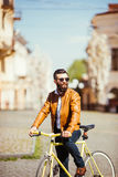 Confident young bearded man in sunglasses riding on his bicycle along the sunny street Royalty Free Stock Image