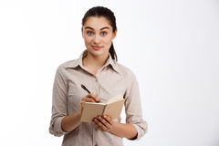 Confident young beautiful businesswoman writing in notebook looking at camera smiling over white background Stock Images