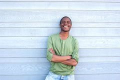 Confident young black man smiling with arms crossed Stock Image