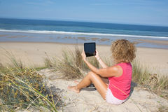 Confident young blond woman make selfie at the beach. Royalty Free Stock Images