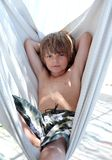 Confident young boy sitting in hammock on vacation Royalty Free Stock Photography