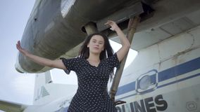 Confident young brunette girl in black dress looking at the camera sitting on the landing gear of the white plane stock video