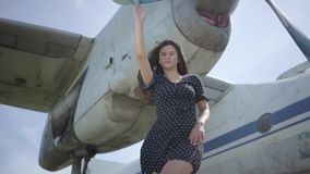 Confident young brunette girl dressed in a black dress looking at the camera in front of the white plane touching. Joy stock video