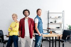 Confident young business colleagues standing together and smiling at camera in office royalty free stock photos