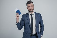 Confident young business man in classic black suit, shirt hold passport, boarding pass ticket isolated on grey wall background in stock photography