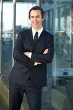 Confident young business man smiling outdoors. Portrait of a confident young business man smiling outdoors with arms crossed Royalty Free Stock Photos