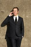 Confident young business man talking on mobile phone outdoors royalty free stock photography