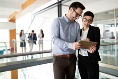 Confident business partners walking down in office building and talking royalty free stock images