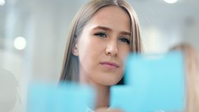Confident young business woman stick colored sticky notes on glass board looking and brainstorming. Close-up portrait of confident young business woman stick stock footage