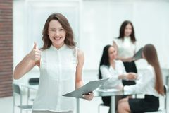 Confident young business woman with clipboard on the background of business team stock image