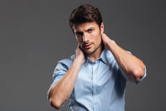 Confident young businessman in blue shirt touching his neck Royalty Free Stock Images