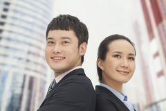 Confident young businessman and businesswoman standing back to back, smiling Royalty Free Stock Photo